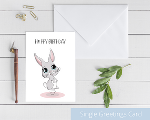 Poppleberry A6 folded birthday card, with a smiling grey bunny illustration, on white cardstock and white envelope.