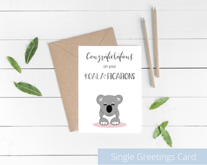 Poppleberry A6 folded congratulations card, with a smiling koala digital illustration, on white cardstock and kraft brown envelope.