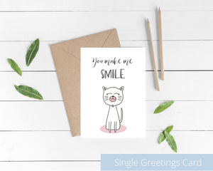 Poppleberry A6 folded greetings card, with a smiling white cat illustration, on white cardstock and kraft brown envelope.
