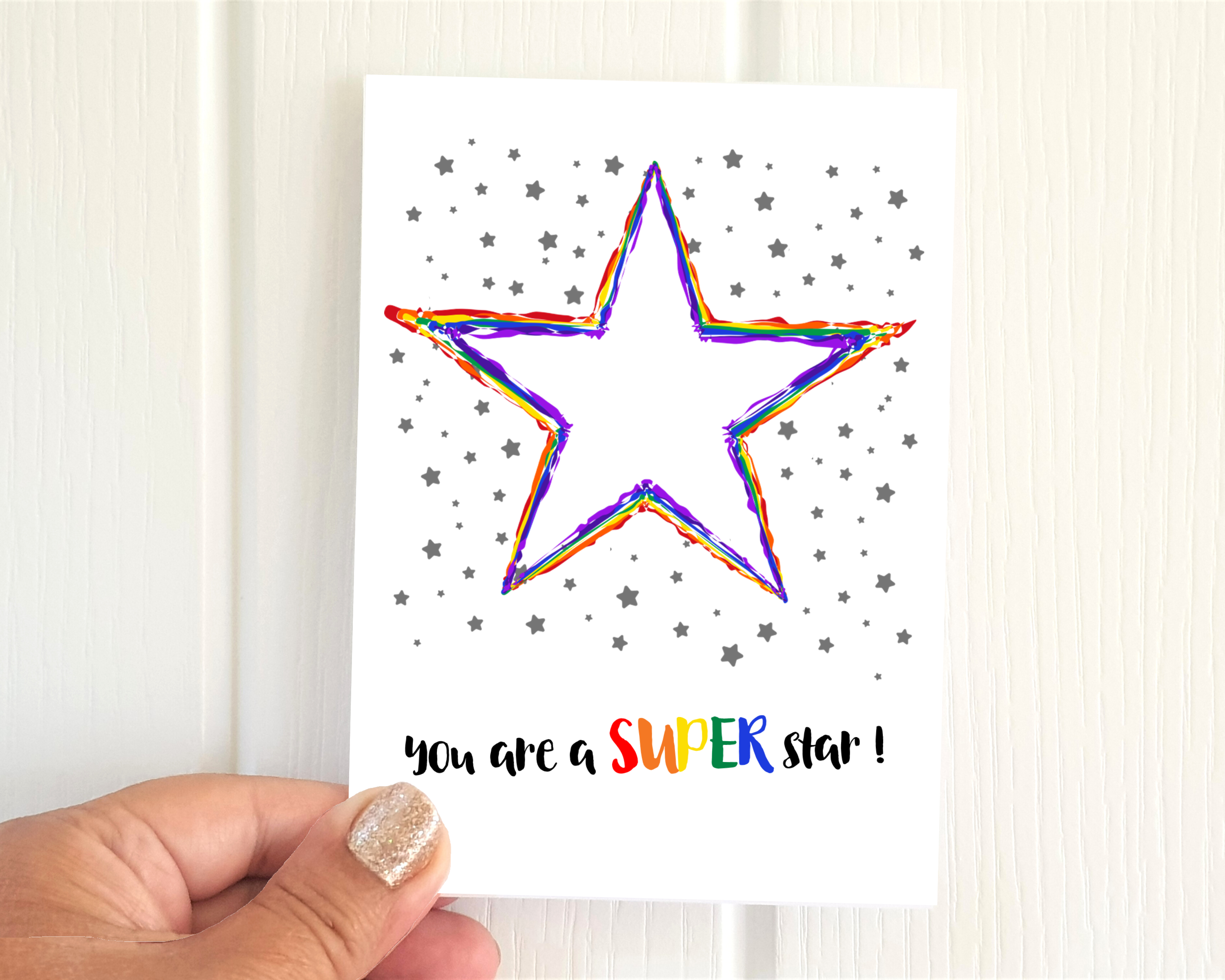 Poppleberry A6 folded greetings card, with a rainbow-coloured star illustration, on white cardstock, size compared with hand.