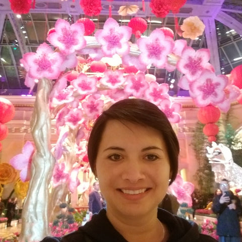 Photo of Gina (the owner of the Fantastic Gifts) smiling with flowers in the background