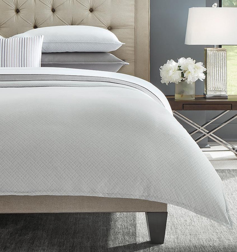The left corner of a grey SFERRA Abriana Duvet Cover with shams and a striped decorative pillow.