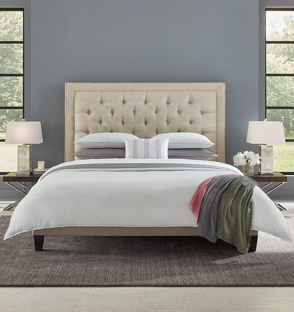 A queen size bed with a grey SFERRA Abriana Duvet Cover, pillows, shams, and a multi-colored throw.
