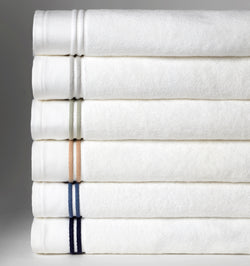 A stack of SFERRA Aura bath towels with multi-colored embroidered striped borders.