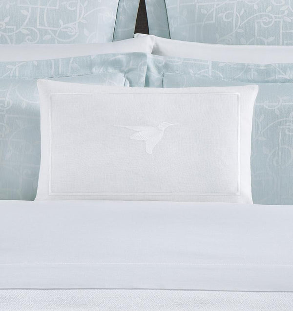 White linen SFERRA decorative pillow with an embroidered hummingbird.