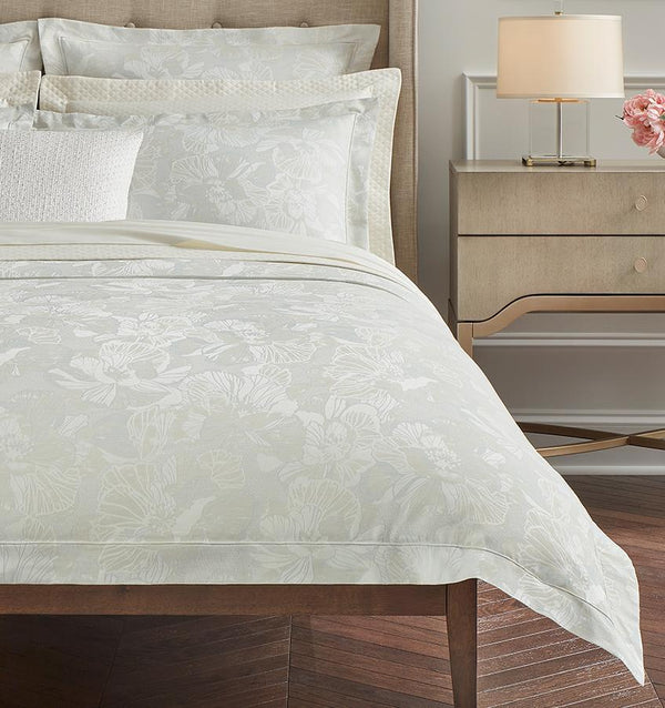 The corner of a bed with the SFERRA Fiore Duvet Cover in pale green with a floral jacquard pattern.