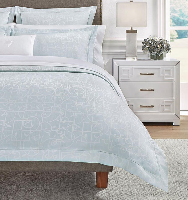 The left side of a bed with a light blue SFERRA Graticcio Duvet Cover woven with a white trellis pattern with matching shams.
