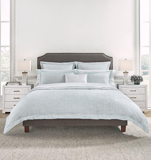 A brown bed in a white bedroom with a pale blue SFERRA Graticcio bedding set.