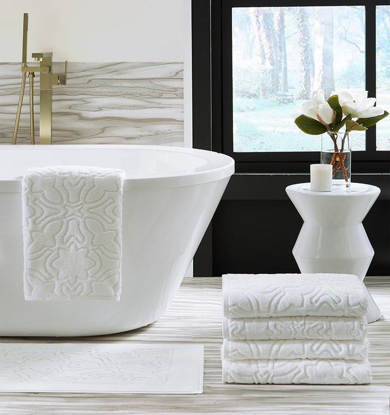 Bath tub with a SFERRA sculpted jacquard towel draped over the side with a stack of towels next to the bath.