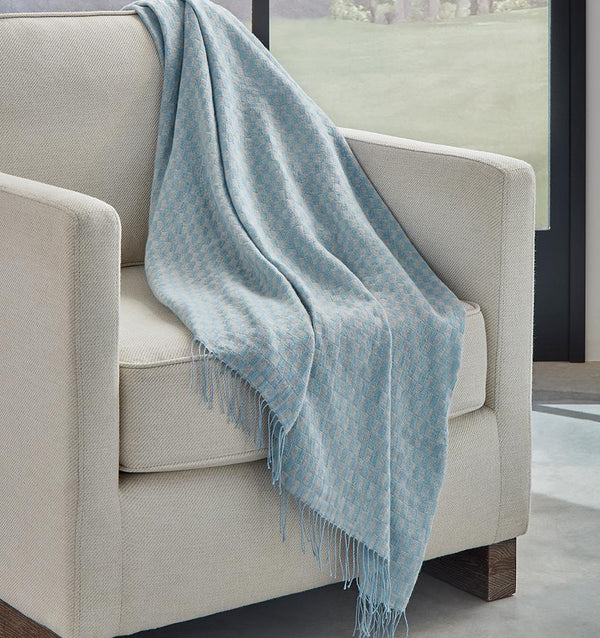 SFERRA Palmilla throw in blue draped over a beige armchair.