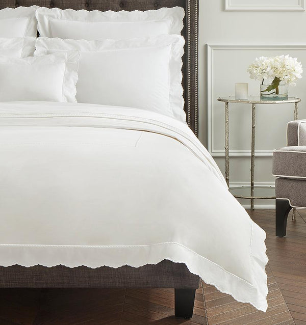 A brown bed with all-white SFERRA Pettine sheets with white scalloped edges.