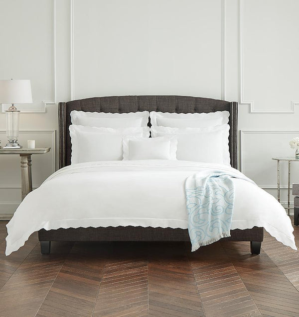 A dark brown bed with white SFERRA percale Pettine bedding with scalloped edges.
