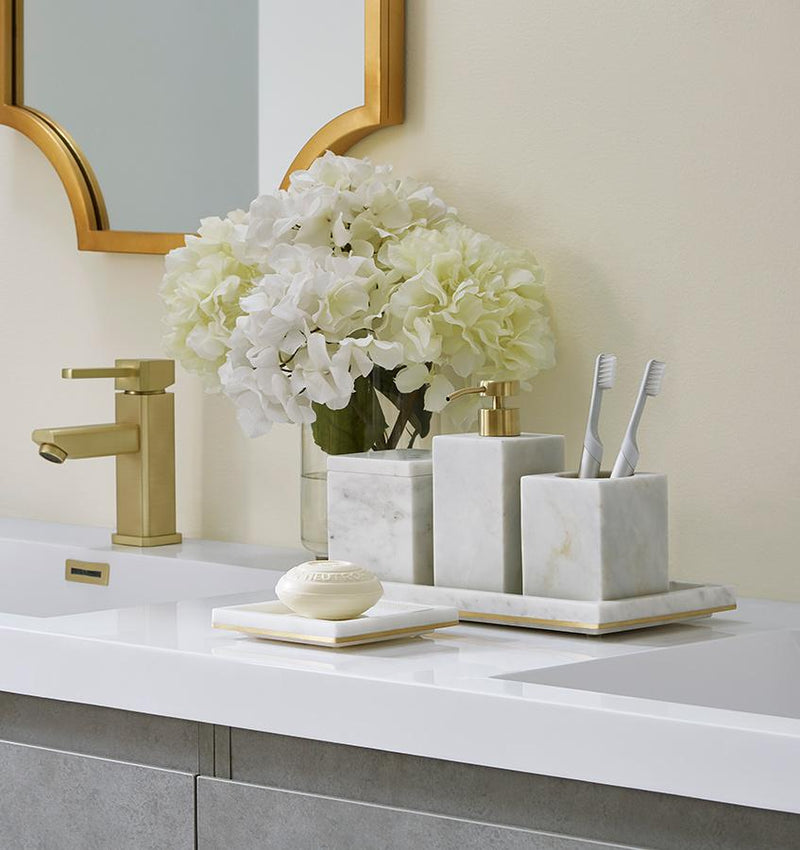 A bathroom counter with gold-trimmed marble SFERRA Pietra bathroom accessories and white hydrangeas.