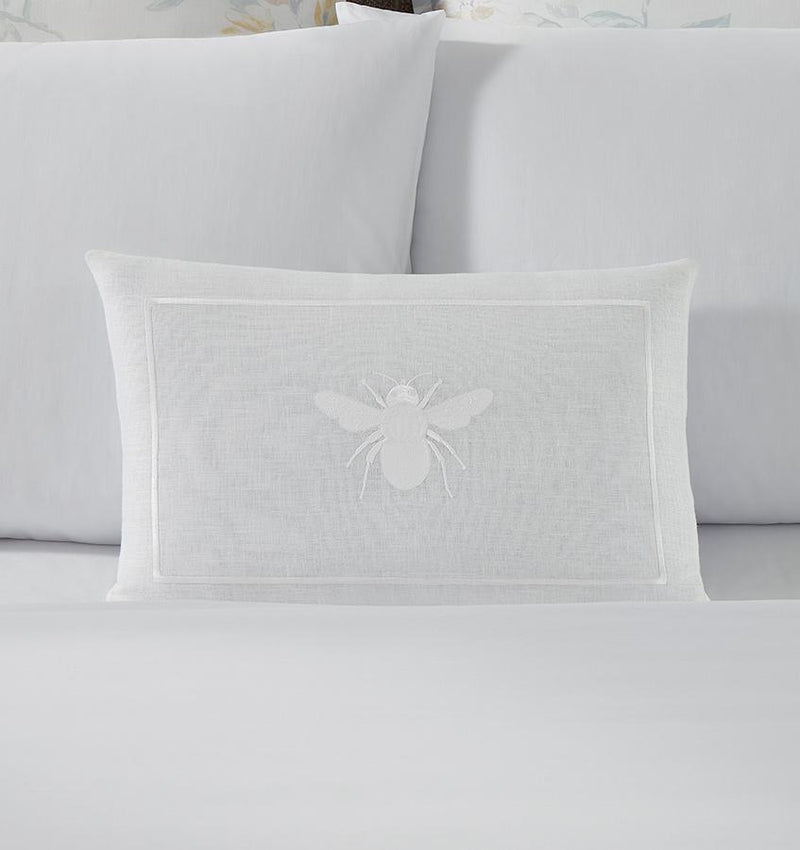 A white linen SFERRA decorative pillow with a white embroidered bee.