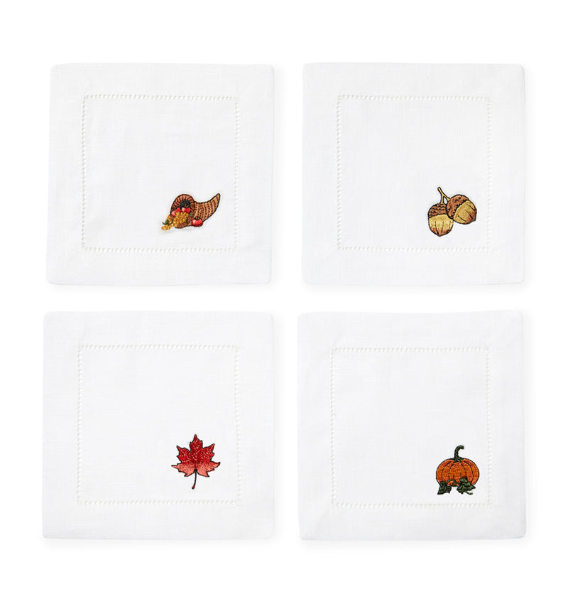 SFERRA Autunno Cocktail Napkins feature fall motifs of an acorn, cornucopia, maple leaf, and pumpkin embroidered on linen napkins.