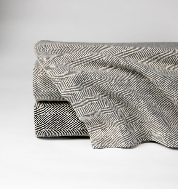 The SFERRA Celine herringbone blanket woven in soft colors with cream.