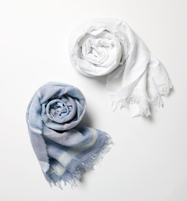 Two SFERRA Garda Scarves rolled up and set against a white background.