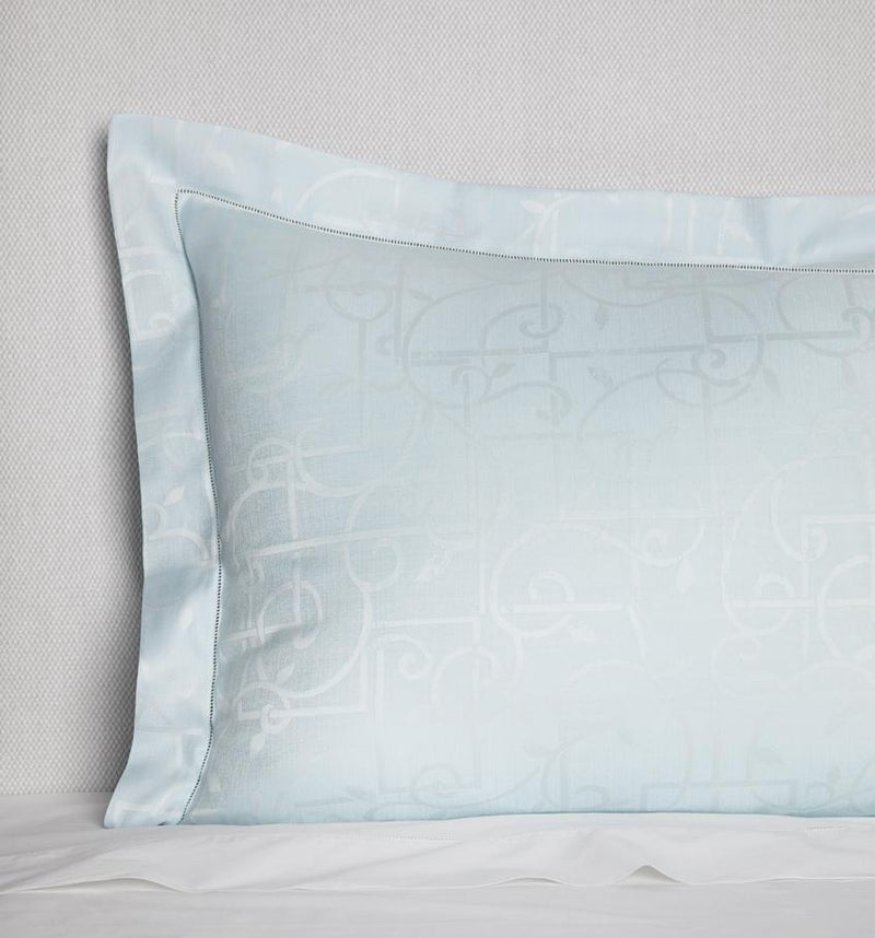 Corner shot of a light blue sateen sham woven with a white trellis pattern against a white background.