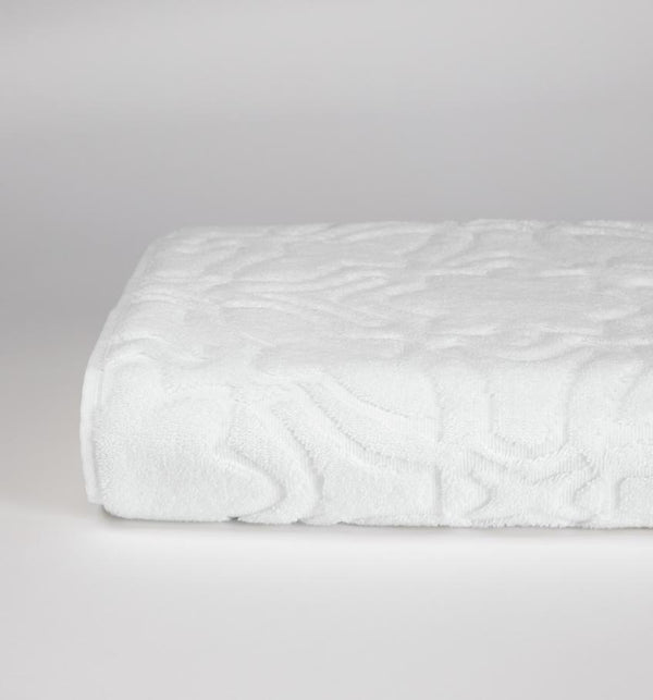 A folded SFERRA sculpted jacquard cotton towel against a grey background.