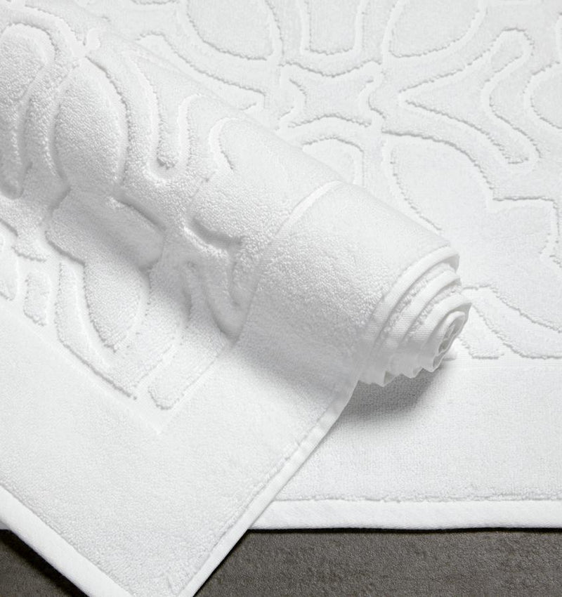 Sculpted jacquard cotton SFERRA Moresco Tub Mat rolled up againsta Moresco Towel.