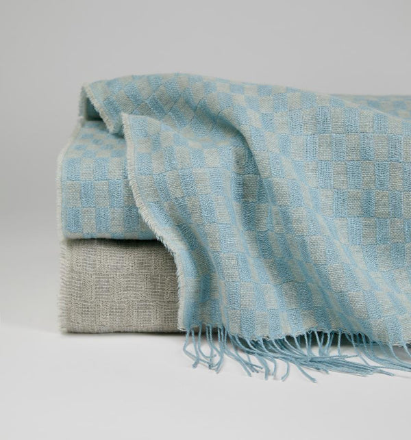 Stack image of the basketweave Palmilla throw in blue and grey against a grey background.