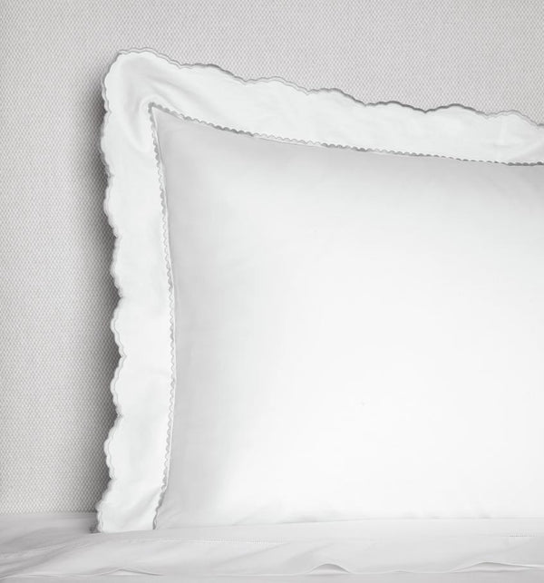 Corner of a white SFERRA Pettine pillowcase with scalloped grey borders against a white background.
