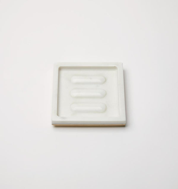 A rectangular marble SFERRA Pietra soap dish against a grey background.