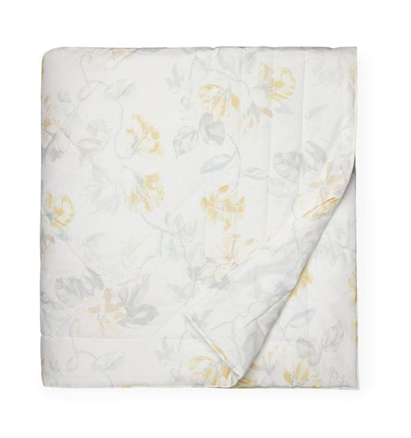White quilted cotton quilt with a light yellow floral motif against a white background.