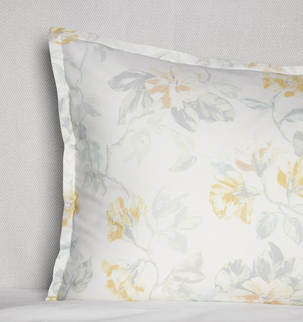 Corner shot of a white cotton sham with a light yellow floral motif against a white background.