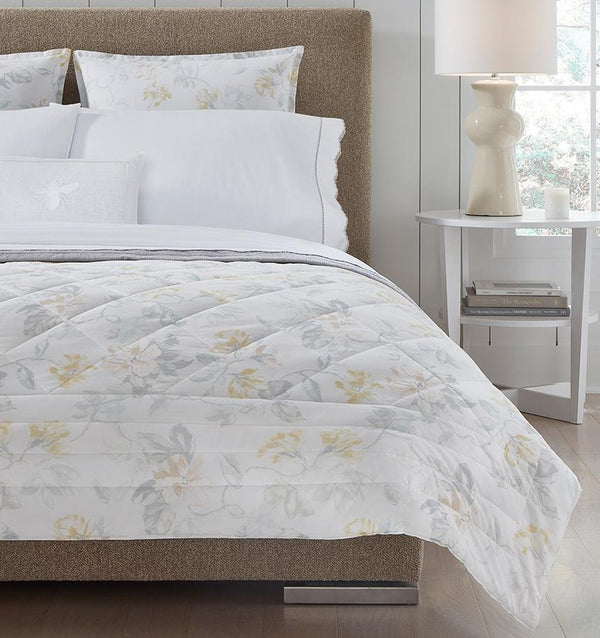 Brown bed with white quilted cotton bedding with a light yellow floral motif.