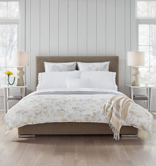 Brown bed with white cotton percale bedding with a light yellow floral motif.