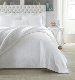 SFERRA Adelli prewashed textured cotton Coverlet on an all-white bed.