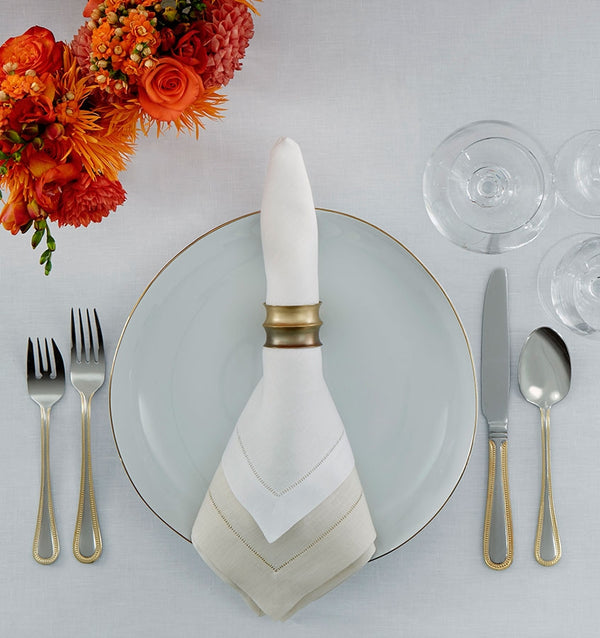 The SFERRA Classico fine linen napkin wrapped with a napkin ring sitting on a table setting.