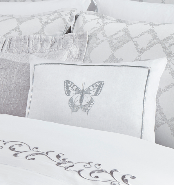 Papilio features a breathtaking butterfly embroidered on a white linen-based decorative pillow.
