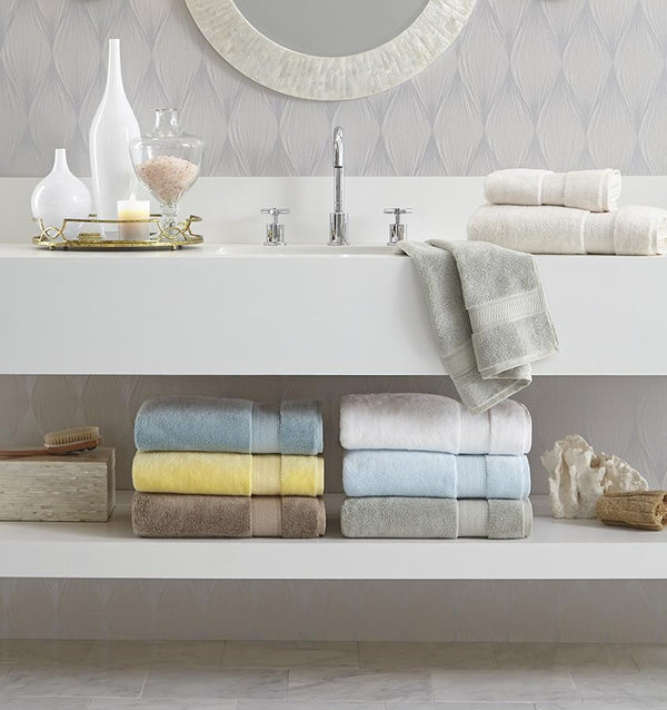 A bathroom with multi-colored SFERRA luxury bath towels stacked under the sink.