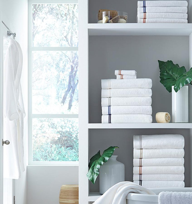 Stacks of SFERRA Aura bath towels with multi-colored embroidered striped borders.