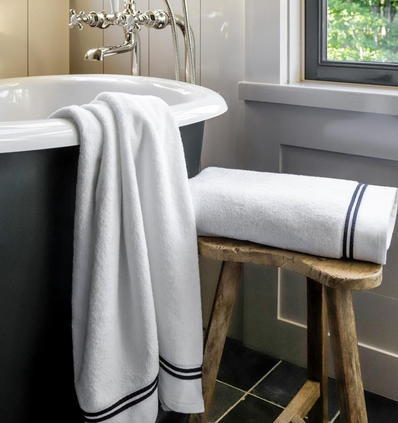 SFERRA Aura bath towels with multi-colored embroidered striped borders draped over a bath tub.
