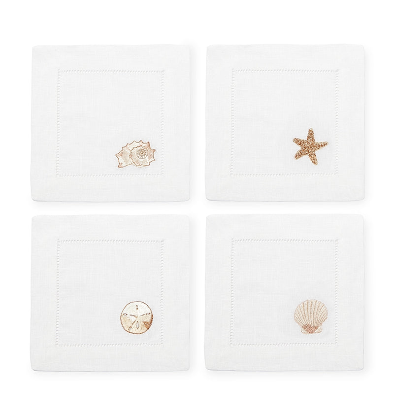 SFERRA Beachcomber cocktail napkins feature four delightful seashell embroideries in golden hues on hemstitched linen napkins.