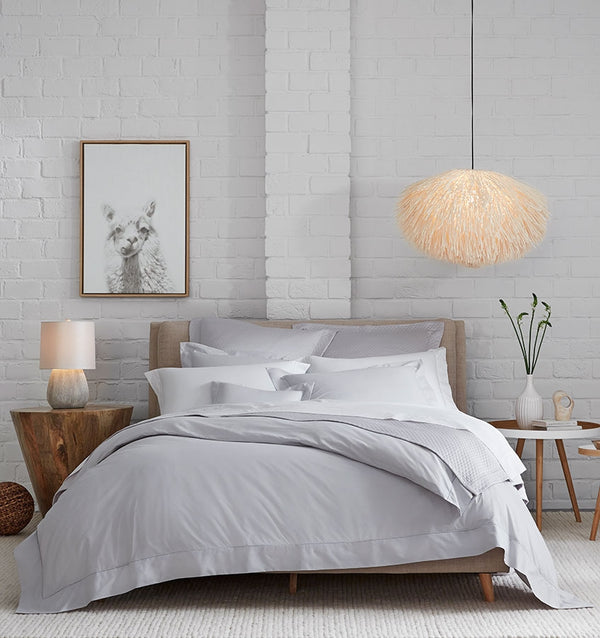 A bed with SFERRA Celeste percale bedding, woven in Italy from pure, extra-long-staple cotton for a super soft hand.
