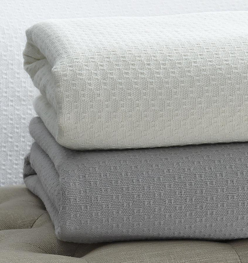 The SFERRA Corino lightweight, breathable cotton blanket in white, ivory, seagreen, and powder blue.