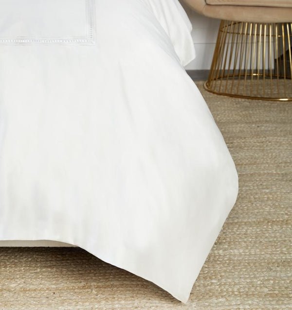 On the Diamante Duvet Cover, a macramé lace inset is threaded through its center with a thin, satin ribbon that frames the border of sateen.