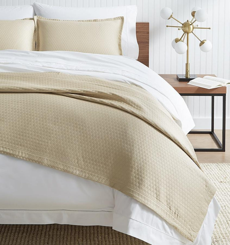 SFERRA Favo Coverlet in beige with a honeycomb pattern.
