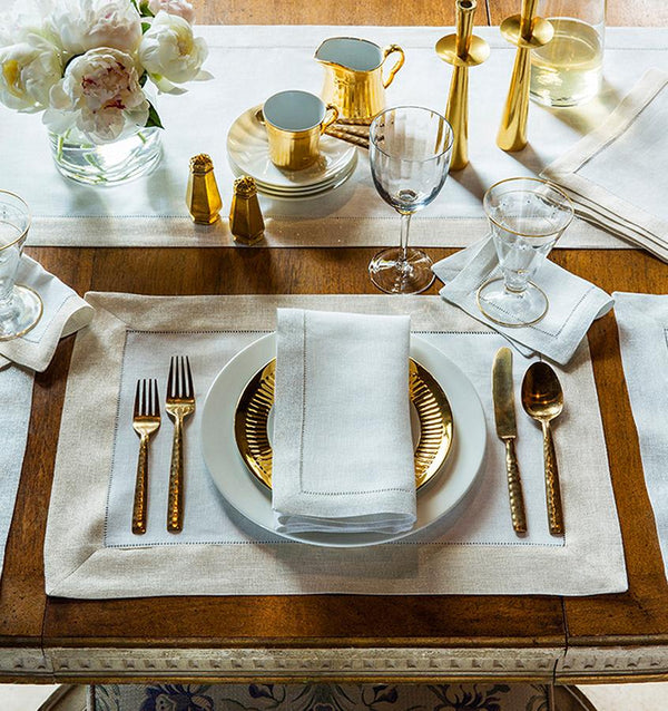 A fall tablescape featuring SFERRA Filetto table linens and gold serveware accents.