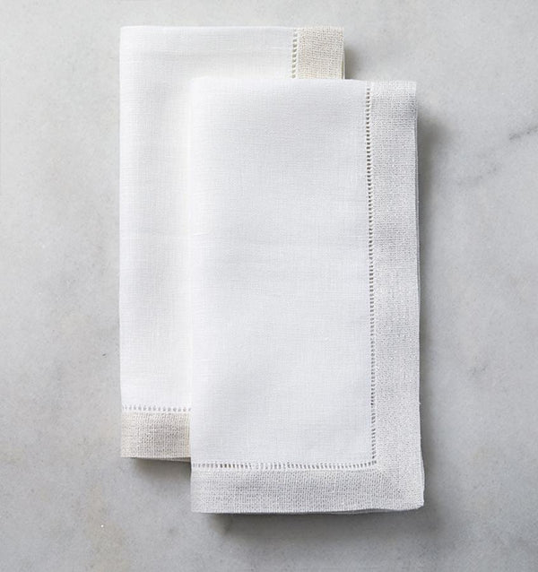 Two folded SFERRA Filetto dinner napkins against a white marble background.