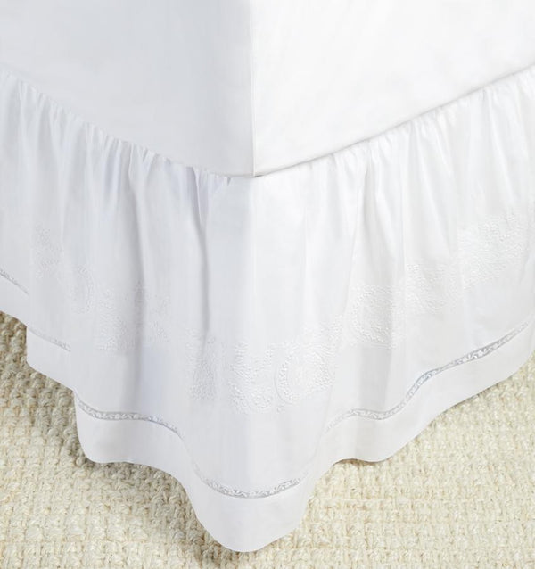 A luxury SFERRA Francesca bed skirt in a white hand-embroidered cotton with a lace inset.