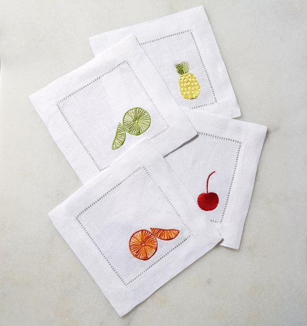 SFERRA Frutta cocktail napkins feature ambrosial fruits on white hemstitched linen napkins.