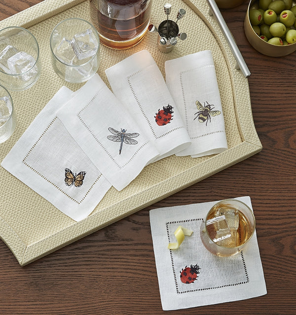 SFERRA Insetti cocktail napkins feature endearing insects on white hemstitched linen napkins.