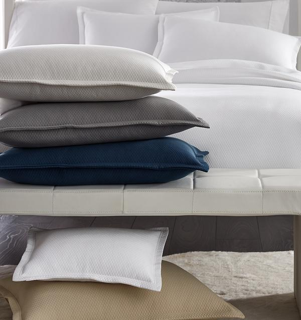 SFERRA Perrio Coverlet with a stack of Perrio Shams