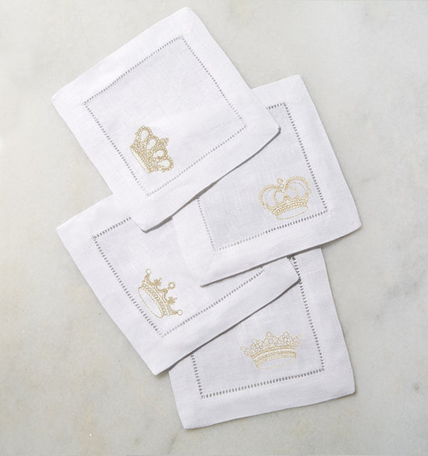 SFERRA Royalty cocktail napkins feature gold crowns on white hemstitched linen napkins.