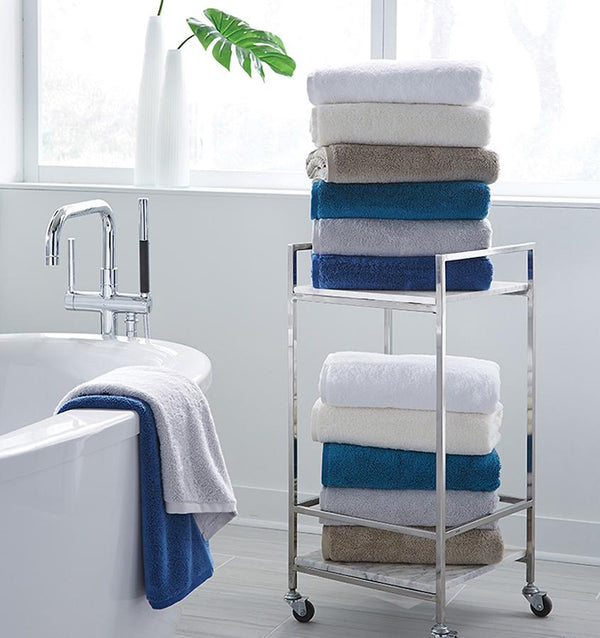 A bathroom with stacks of SFERRA Sarma bath towels in white, ivory and shades of blue.